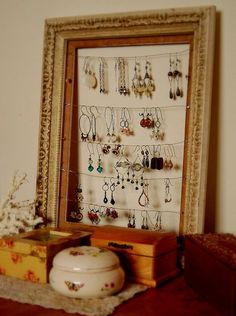 An old vintage frame (once discarded and almost thrown away due to chips and scratches)  has been given a new life by way of earring display. To make one yourself, simply place small nails down the back sides of the frame, and string wire across to each nail. Easy peasy, and now showcases all of my favorite