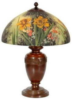 lighting, Connecticut, A Handel glass Daffodil reverse painted table lamp, No. 7122 and artist signed HR (Hattie Runge), domical shade, reverse painted with vibrant yellow daffodil flowers with leaves, pink background  flowers and a silhouettedbackground in green, gray and black tones, bulbous Handel urn styles having a border with square rosettes spaced between a gelmetric band, has a spherical 3 socket light cluster with acorn pulls. Circa 1901-1930