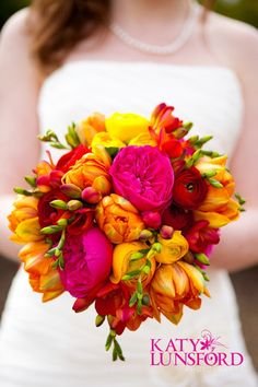 Bright pink, yellow & orange wedding decorations..mixed with a dark red.