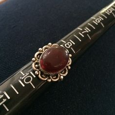 Vintage sterling silver size 9 ring A deep red stone surrounded by sterling silver. Includes the vintage jewelry box pictured. Vintage Jewelry Rings