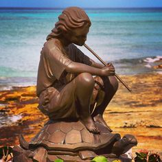 Girl sitting on a turtle and playing her flute. #staues in #cozumel