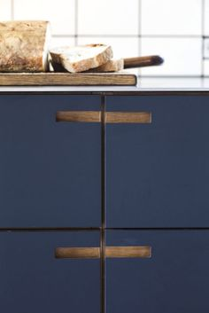 Love the ?oak? cabinetry with blue painted drawer fronts and integrated pulls/cut outs for handles.: