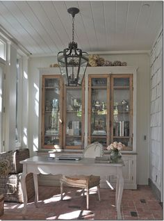 I never would have thought to turn an enclosed back porch into a study.  Lovin' the brick floor.