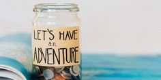 """Mixed denomination and currency coins in a glass jar with handwritten label """"Let's Have An Adventure"""""""