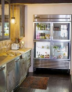 Love this contradiction of rustic cabinets and floors with sleek, modern stainless refrigerator.