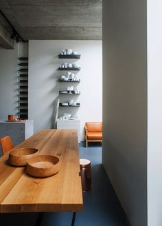 Nice dining room idea with large wood table, open shelves and white walls