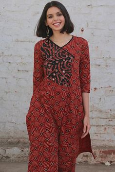 Earthy hues of brick and terracotta, hand block printed with motifs in black, accentuated with appliqué work and mirror work embroidery, makes this elegant design an Okhai must have! With its flattering neckline, flowy silhouette and 2 pockets, this kurta is ideal for officewear, vacations and even festive events, as i Silk Kurti Designs, Simple Kurta Designs, Salwar Designs, Kurta Designs Women, Salwar Pattern, Kurta Patterns, Dress Patterns, Dress Neck Designs, Blouse Designs