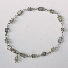 """Tiny faceted irridescent labradorite beads wired together with sterling silver wire and a sterling silver lobster clasp. 7 1/4"""" long dainty little bracelet with a labradorite charm at the clasp. We ca"""