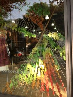 This autumn window display is very effective display and would translate well to a craft show booth.  The diagonal lines from the strings create energy and catch the eye. It is low cost. Notice the way they use the stick to redirect the lines. These principles could be reinvented in a cost effective manner to feature your work. Put the stick in the corner of your booth and expand to the sides and back.