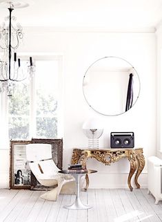 Glamorous seating area with modern furniture and antique gilded console