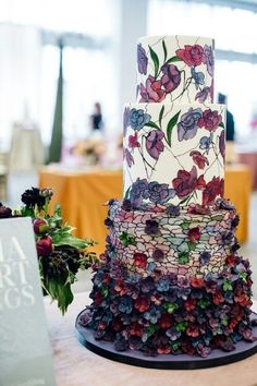 Gorgeous wedding cake covered in stained glass and flowers. Love the purple and maroon/burgundy shades too.
