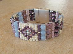 This beautiful cuff bracelet has a distinct Southwestern flair with the diamond patterns I have created with the seed beads. This is woven