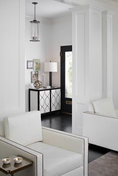 love the chairs with the nail-head trim and the black/white cabinet in the entry...