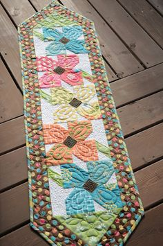 Pinwheel Posies Runner. This is probably my favorite quilting of all three, as I liked how the double loop design shows up in each flower.