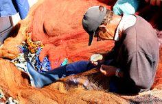 Fisherman mending fishing nets at Porto de Baleeira, Sagres
