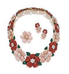 SUITE OF RED & PINK CORAL & DIAMOND 'ROSE DE NOEL' JEWELRY, VAN CLEEF & ARPELS, PARIS.  Necklace composed of alternating red & pink coral flowers, the centers decorated with clusters of round diamonds, the leaves of dyed green chalcedony, a brooch with petals of pink coral, the center set with a cluster of round diamonds, & a pair of earclips, each composed of a diamond-centered pink & red coral blossom, mounted in 18 karat gold, signed