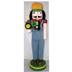 This nutcracker is perfect for the farmer. He has on blue denim overalls with a red t-shirt. He is holding a green and yellow tractor. To complete his look he is wearing a yellow and green cap and stands on a round yellow and green base.