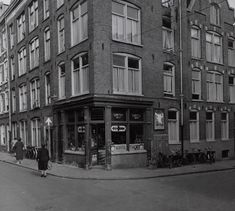 1950's. A view of the Kleine Kattenburgerstraat in Amsterdam. At the corner grocery store De Pijl. The old buildings, as shown in the photograph, were demolished in the 1950's and 1960's. In the 1970's the neighborhood was rebuilt with new residential and student housing units. #amsterdam #1950 #KleineKattenburgerstraat