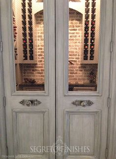 These newly built wine room doors were finished to appear old and include a wire mesh insert on top to give a peek into the beautiful room beyond!
