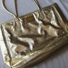 """Victoria's Secret Large Gold Croc Tote Has some wear on the bottom corners and handles are cracked. Scuff marks on base. Measures 18"""" wide at top, 12"""" tall and 4"""" deep. Strap drop is 10."""" Has been used a lot but still has some life left. Victoria's Secret Bags Totes"""