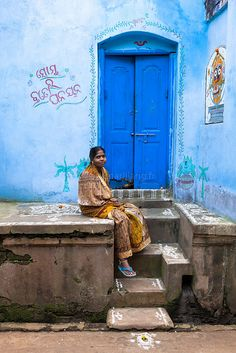 Woman sitting in front of her blue house decorated with hand-paintings and Jagannath.Puri, Orissa, India.