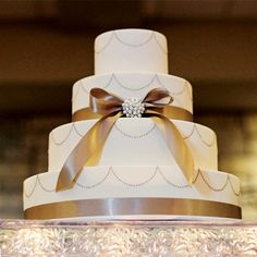 Champagne ribbon and a pearl brooch decorated the ivory cake.  This is perfect!! champagne, gold, ivory, metallics, winter