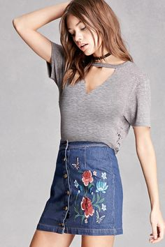 A denim mini skirt featuring a floral embroidery and an exposed button front. This is an independent brand and not a Forever 21 branded item.