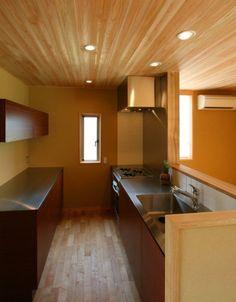 自然素材を随所に使用した本物志向の木の家。床はメープルとクリ、天井はサワラとスギ、壁は土壁(珪藻土)を使っている。  敷地が変形していたので、それに即した合理的な平面プランを提案したが、施主が斜めの壁に抵抗を感じたので、全体を単純な長方形とした。屋根も三角の切妻なので外観は普通の家になった。  特徴は居間の大きな開口部(2.3m×4.8m)である。木製建具を丹念につくり、庭と居間を一体とすることで、豊かな広がりを与えることができた。庭が完成すれば、緑あふれる魅力的なリビングになると考えている。  キッチンはアムスタイル社製の特注品、ガラスは防犯ペアガラス、ガラス庇はデバイス社製、床暖房はノーリツ社製、断熱材は住宅金融公庫仕様の2倍を充填し、外壁には通気層を確保している。