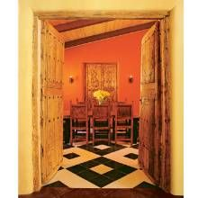 The dining room is resplendent with vibrant color, a Mexican concrete tile floor and an alacena with antique doors. Wrought-iron lockplate designs reminiscent of those found on Spanish Colonial trunks form the wall sconces. The doors to the room are antiques from Mexico.