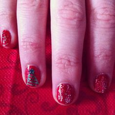 Red manicure with red sparkle top coat and Christmas tree feature, topped with green star gem.