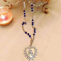 Long Silver Juicy Necklace This is a very chic piece that features a large crystal encapsulated heart that reads Life is Juicy. There is a hint of light blue around the heart and a royal blue stone on the necklace. This is a long piece that can be worn with virtually anything. It is about 15-16 inches in length. Juicy Couture Jewelry Necklaces