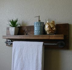 Handmade bathroom shelf with industrial style graphite finish towel bar. A perfect addition to any home bathroom or apartment.  Made from solid wood. It has been lightly sanded down, then stained and sealed with a beautiful dark walnut finish.  This piece does not include the accessory items as shown in the pictures.  The color of the stained wood captured in the photos might vary slightly.  Dimensions: 29 in wide x 9.25 in tall x 4.25/6.25 in deep (shelf 3.5/5.5 in deep x 27 in long)…
