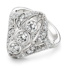 18ct White Gold Diamond Ring      3 round brilliant cut diamonds in rub over settings embellished by 30 round brilliant cut diamonds, grain set, taper into a narrow half round band.   All setting edges are millegrained. engagement-rings