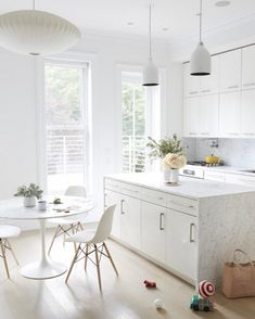 All-white and marble kitchen with modern lights and small, modern dining space