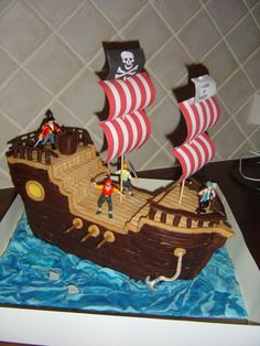 "Another pinner wrote: This cake used three 10""x10"" madeira cakes stacked and carved - for thirty 6yo boys! Sugarpaste everywhere, except the pirates and the sails. It was a nightmare - it was so hot the brown sugarpaste woudn't harden! Used lots of ideas from this site - the cannons, the sails, the anchor, the sharks...this site is a treasure chest...:)"