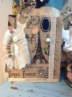 Very saddened by what has happened in Paris that even though I have created many items with the Paris theme this one touched my heart as I placed the burlap on a old book cover to the darling court style dress that is hand made with a old book paper bodice with lace straps. As well as vintage hankies and lace. Millinery leaf and vintage metal enamel white rose pin with old crystal pins as well. 11x9