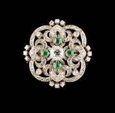 A diamond and emerald brooch. Set with one old mine cut diamond weighing approx. 1,15ct (H~J, SI), 36 old mine and single cut diamonds (ca. 0,65ct), rose cut diamonds and four emeralds, Portugal, 20th century, Dim.: 3,7 x 3,7 cm, 16,6 g