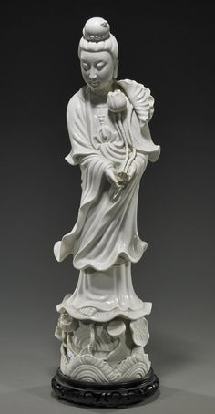 """Tall Chinese, blanc de chine porcelain model of Guanyin; standing in long robes atop a lotus pedestal and carrying a lotus flower; H: 23 1/2"""", wood stand"""