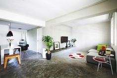 Cement screed flooring and white walls provide an edgy yet neutral backdrop for designer furniture like the Air Break stool in the dining area as well as Fritz Hansen Alphabet sofa.