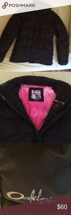 Down Oakley Coat Super warm ski/snowboard jacket. Exterior is entirely black, inside lining is hot pink. Has a removable snow skirt at the waist to keep out cold drafts and snow. Has a rubber hole to keep your head phones secure and hidden on the inside. Zips up in the front and magnetic snaps hide the zipper. The magnetic snaps are also so convenient to close in a hurry!. Mesh armpit vents for air circulation can be zipped or unzipped for temperature control. Two outside pockets and one…