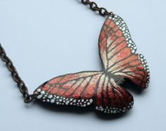 Its monarch butterfly season. Celebrate autumn with this painted butterfly in shimmery tones of red, orange, and gold. This necklace features a large monarch butterfly pendant made of a gourd piece that was cut, sanded smooth, stained with a dark walnut wood stain, painted with metallic