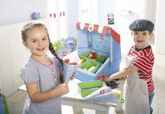 """Kaufladen """"Gutes Gemüse"""" - Was darf's denn sein? Kartoffeln sind heute im Angebot! Dieser schöne Marktstand für knackiges Gemüse ist toll für alle kleinen Markthändler. Er passt in jedes Kinderzimmer und kann dank des Tragegriffs an der Oberseite auch leicht mitgenommen werden. Die Tafel ist beschriftbar und die Waren aus Stoff können in den vier Auslageboxen schön präsentiert werden. Die Tüten und der Satz Münzen machen das Verkaufsspiel perfekt."""
