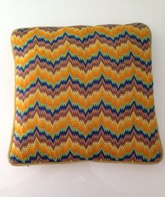 This is a fantastic handmade needlepoint Bargello pillow. It is a flame stitch in varying shades of orange, tan, green, and blue, very reminiscent of a classic Missoni design. The pillow measures 15 x 15 inches, and is backed in yellow velvet, with a metal zipper. There are some small areas of wear- please see photos :) Thanks for looking