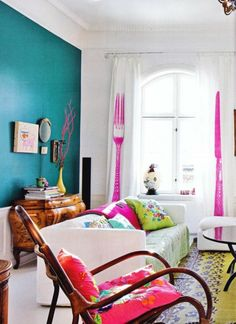 teal anchor wall, knife and fork print curtains, pops of pink, white, and wood living room.