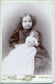 a darling little girl and her bisque doll. It says on the back Mary Edmonds, Taken March, 1895, (I think it also to says, 2  1/2 years old)