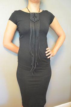 Modern, long, black adjustable bohemian macrame necklace with gold hegaxonal beads.