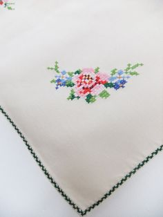 A pretty vintage cross stitch tablecloth with beautiful flowers in pink, red and blue with lovely green leaves. The fabric is cream cotton or linen. The edging of the tablecloth has been sewn in green cross stitch.    The tablecloth measures 33 in x 33in (84cm x 84cm).    The tablecloth is in very good condition. There are a couple of very small stains which are virtually unnoticeable and don't spoil the tablecloth at all. The cross stitch work is very neat and the colours are lovely…