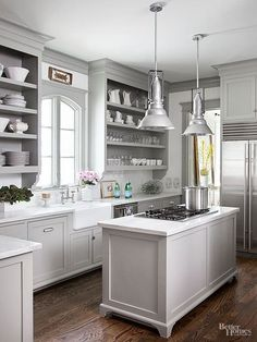 The kitchen's versatile gray base hue coats cabinetry and the island alike while also serving practical purposes. Not only does the neutral color provide more depth than an all-white space, but it also visually enlarges the compact kitchen.
