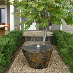 Cut boulder used as water feature in a small space. Pebbles and the Japanese Maple support the serene and uncluttered feel. Framing with low hedge creates a garden room of its own.