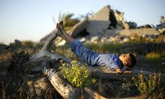 A Palestinian boy, whose house was destroyed during the 50-day war between Israel and Hamas-led militants in the summer of 2014, lies on a tree in the Johar al-Deek neighbourhood in central Gaza City, close to the border with Israel.